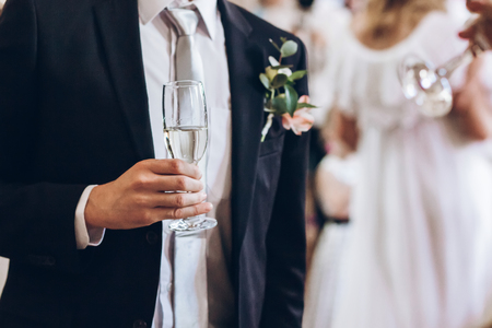 group of elegant people holding glasses of champagne at luxury wedding reception. groom hand toasting and cheering with drinks at social events.  christmas celebration