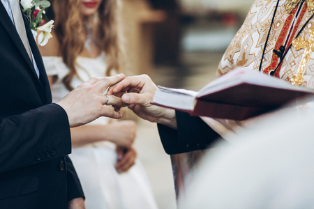 priest putting on wedding rings on groom and bride hand in church during holy matrimony. wedding ceremony concept