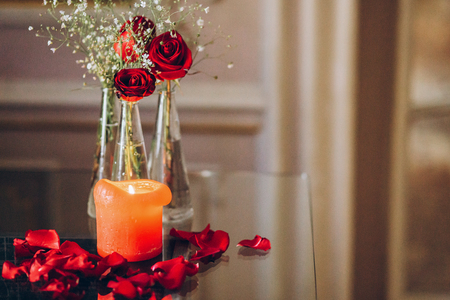 red roses and burning candle wit petals on glass table. luxury decor and addorning at wedding reception. happy valentines day concept. space for text Imagens