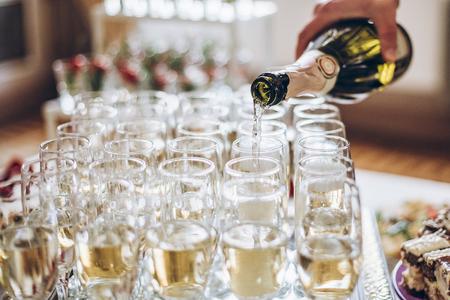 copas de champán dorado. Camarero sirviendo champán en elegantes copas en la boda de lujo. rica celebración