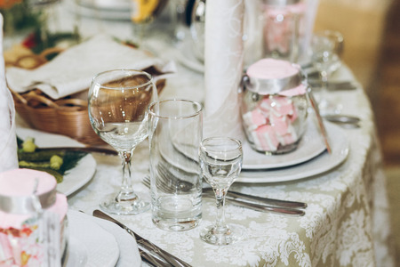 beautiful decorated setting on centerpiece table with stylish plate,glasses,napkin and cutlery at luxury wedding reception in restaurant. wedding favors. stylish decor and catering Banque d'images - 98773196