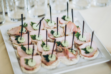 delicious appetizers canape with ham and cucumber on plate on table at wedding reception. luxury catering at celebrations Stock Photo