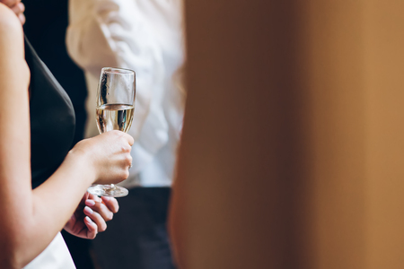 elegant people with glasses of champagne at luxury wedding reception. people toasting with drinks at social events. corporate business celebration. christmas feast