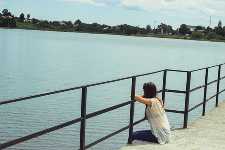 beautiful brunette girl sitting alone on a pier and looking at water in summer vacation Banco de Imagens