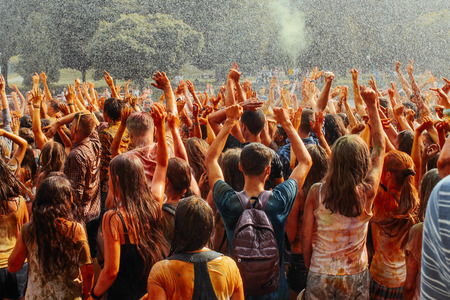 hands and happy people crowd partying under rain at holi fest, festival of colors in summer, amazing moment Stock Photo