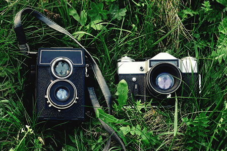 top view on analog photo cameras on the grass, traveling equipment in mountains