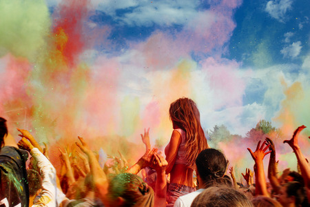 happy people crowd partying under colorful powder cloud at holi fest, festival of colors in summer, amazing moment Stock Photo
