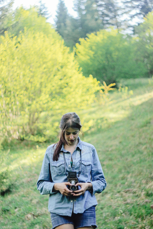 stylish beautiful girl hipster with analog photo camera  in spring sunny mountains, national park