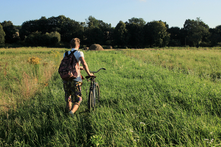 boy holding and riding a bicycle in a field on a sunny summer day, vacation in countryside Stock Photo