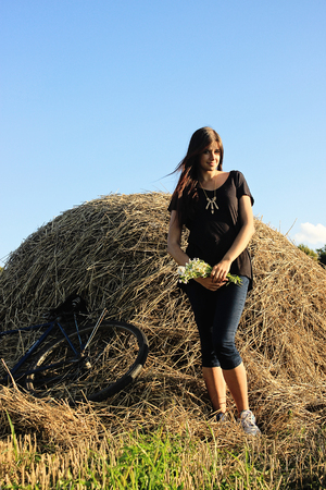 girl holding bouquet of daisy on a background of haystack and bicycle in a sunny summer field 写真素材