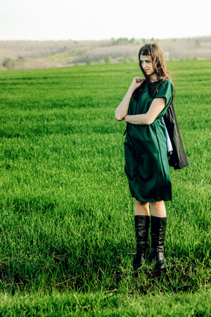 beautiful brunette girl in windy green field, sunny springtime, environment concept Stock Photo