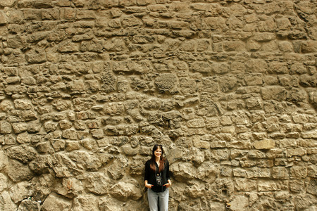 stylish happy woman with analog film camera  on background of city old wall, space for text