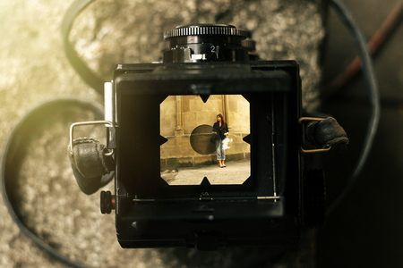 stylish happy woman in viewfinder of  analog film camera on background of city old wall Stock Photo
