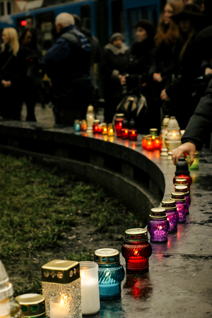 crowd of people lighting candles in city center, mourning victims in terrorism attacks and revolutions, sadness moment Stock fotó