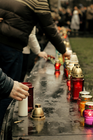 crowd of people lighting candles in city center, mourning victims in terrorism attacks and revolutions, sadness moment Stock Photo