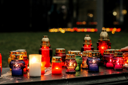 many colorful candles with light burning in city center on marble stone, memorial day and sad bereavement moment