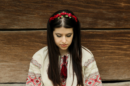 beautiful brunette woman in national ukrainian embroidery clothes on background of old native wooden house