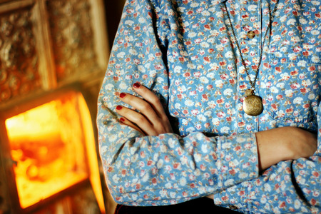 woman in rustic floral shirt and pendant crosses hands on background of cozy fireplace Stock Photo