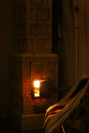 warm fireplace and wooden chair with woolen native blanket, cozy winter holidays