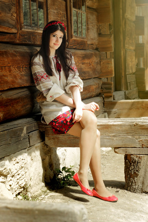 beautiful brunette woman in national ukrainian embroidery clothes on background of old native wooden house Banco de Imagens - 99184473