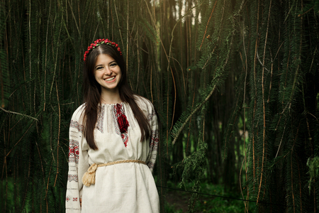 beautiful happy woman in national ukrainian embroidery clothes smiling on background of tree Stock Photo
