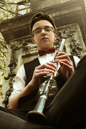 stylish hipster sitting man playing clarinet  on background of old city street, close up Stock Photo