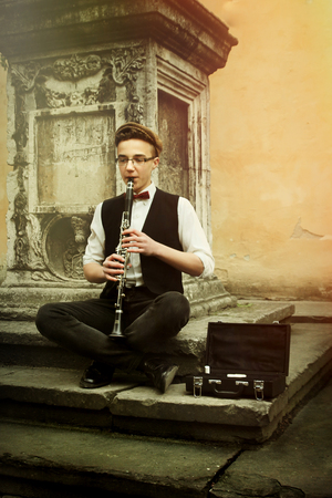 stylish hipster man playing clarinet on background of old city street