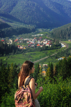 happy beautiful girl hipster with backpack, looking at city down the hill on background of amazing sky and mountains in summer