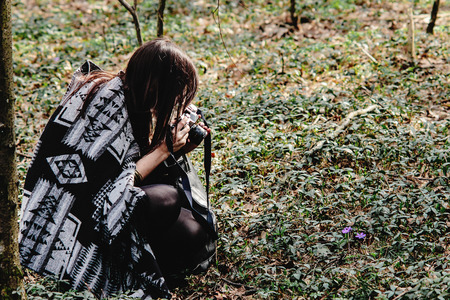 beautiful brunette woman in boho poncho taking photos on analog photo camera in spring forest