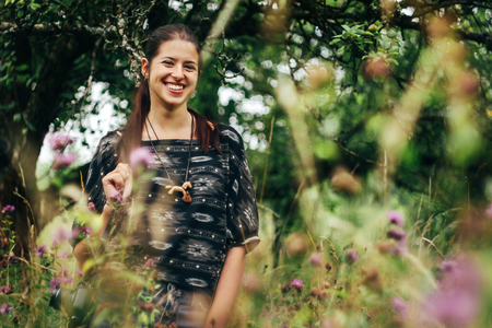 happy stylish woman hipster with photo camera among trees on background of woods in summer Stockfoto