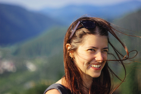 happy beautiful girl hipster laughing on background of amazing sky and mountains in summer