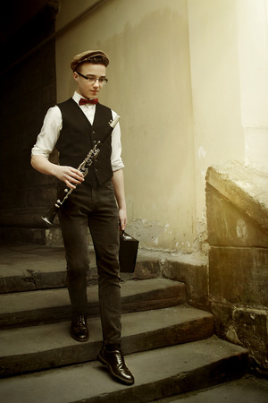stylish hipster man holding clarinet and walking with case on background of old city Stock Photo
