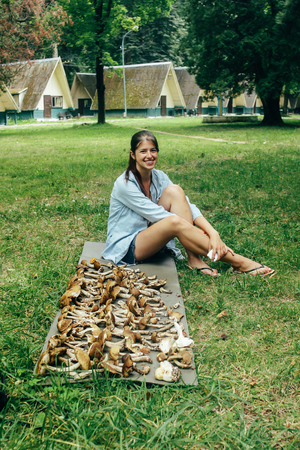 happy stylish girl traveler sitting at pile of gathered mushrooms and smiling, leisure in summer mountains