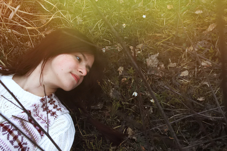 stylish brunette girl traveler lying with snowdrops on the background of mountains in spring time