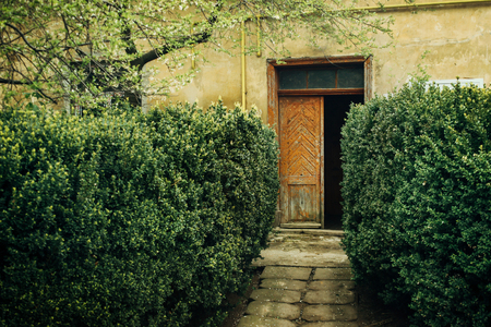 old rustic building with wooden doors and geen garden, italian patio abbey, romantic place to see