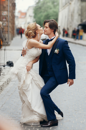 stylish bride and groom dancing and having fun in city street. happy luxury wedding couple holding hands in light. romantic sensual moment.  emotional man and woman