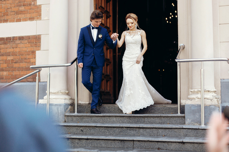 stylish bride and groom walking out of church after holy matrimony. happy luxury wedding couple during wedding ceremony. romantic moment. spiritual love