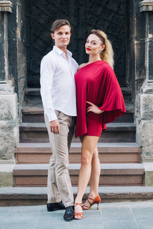 beautiful happy couple in love posing at old building in sunny street. stylish hipster groom and blonde bride in red dress gently hugging, professional dancers. romantic moments in summer