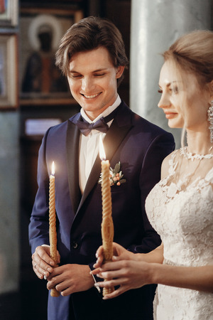 stylish bride and groom holding candles at holy matrimony in church. happy luxury wedding couple during wedding ceremony. romantic moment. spiritual love
