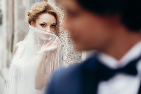 Luxushochzeitspaare, die am Altbau im Licht aufwerfen. stilvolle Braut und Bräutigam, die in der Stadtstraße schauen und umfassen. romantischer sinnlicher Moment. Frau, die Mann unter Schleier betrachtet Standard-Bild