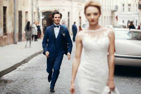 stylish bride walking and groom running after her in city street. happy luxury wedding couple having fun and dancing . romantic  moment.