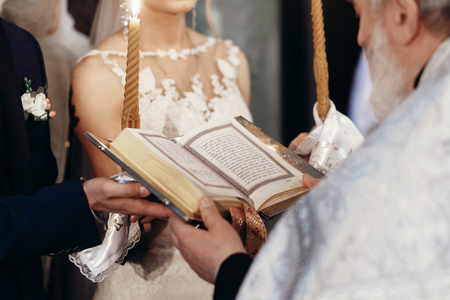 priest holding gospel. stylish bride and groom holding bible with priest at holy matrimony in church. spiritual love couple during wedding ceremony. Archivio Fotografico