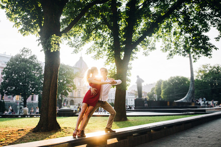 beautiful happy couple in love embracing and dancing in evening sunlight in sunny street. stylish hipster groom and blonde bride performing dance, professional dancers. romantic moments in summer
