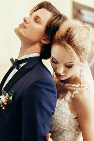 stylish bride and groom posing and hugging in hotel room. happy luxury wedding couple embracing. romantic passionate sensual moment. woman and man together Stockfoto