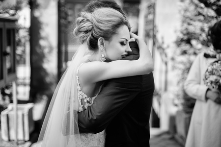 stylish bride and groom gently hugging after holy matrimony in church. happy luxury wedding couple embracing. romantic moment. spiritual love Stock Photo