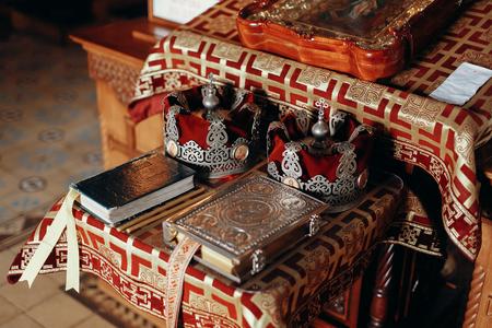 結婚式で教会の赤と金の祭壇に金の聖書、福音、王冠と十字架とアイコン
