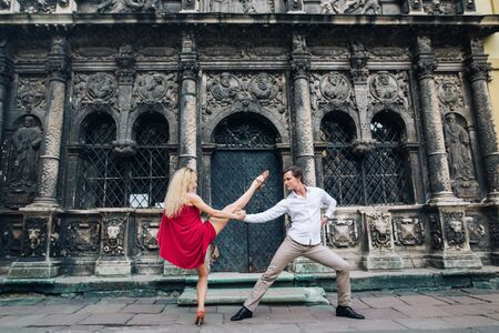 beautiful happy couple in love embracing and dancing at old building in sunny street. stylish hipster groom and blonde bride in red dress performing dance, professional dancers. romantic moments