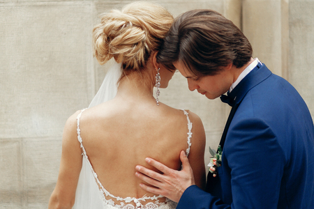 luxury wedding couple embracing at old building in in light. stylish bride and groom kissing her back  in city street. romantic sensual moment. man tenderly touching woman Stock Photo