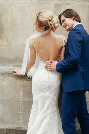 Stilvolle Braut zurück und Bräutigam, die in der Stadtstraße umfassen. glückliche Luxushochzeitspaare, die am Altbau im Licht umarmen. romantischer sinnlicher Moment. Frau und Mann lächeln und küssen Standard-Bild - 99528533