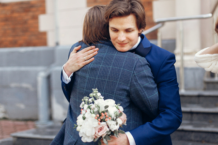 stylish groom hugging father or brother after holy matrimony in church. happy family moments. spiritual love. happy fathers day concept